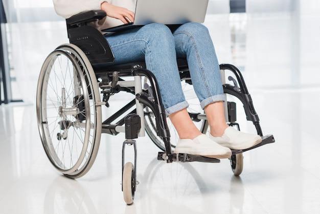 Niedriger abschnitt einer behinderten frau, die auf rollstuhl unter verwendung der digitalen tablette sitzt