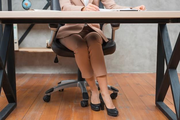 Niedriger abschnitt einer geschäftsfrau, die auf stuhl am arbeitsplatz sitzt