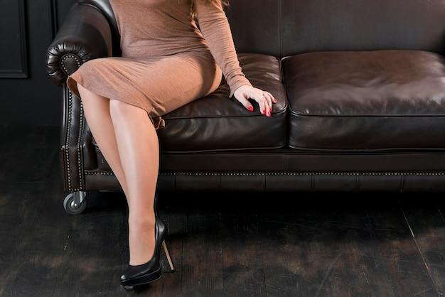 Niedriger abschnitt einer jungen frau mit den schwarzen hohen absätzen, die auf sofa sitzen