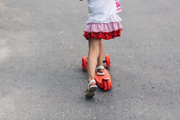 Niedriger abschnitt eines mädchens, das trittroller auf straße reitet