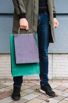 Niedriger abschnitt eines mannes, der auf der pflasterung in der hand hält bunte einkaufstaschen steht