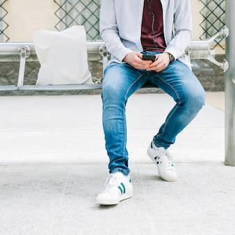 Niedriger abschnitt eines mannes, der smartphone verwendet
