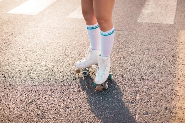 Niedriger abschnitt eines tragenden rollschuhs der frau, der auf asphalt steht