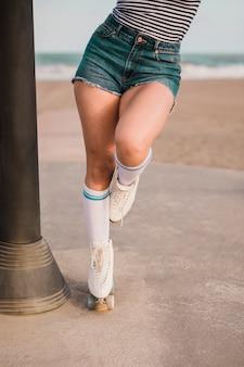 Niedriger abschnitt eines weiblichen schlittschuhläufers, der auf einem bein steht