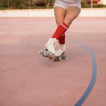 Niedriger abschnitt eines weiblichen schlittschuhläufers, der auf gericht eisläuft