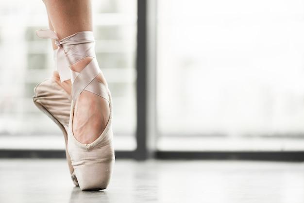 Niedriger abschnitt von den tragenden ballettschuhen des weiblichen tänzers, die an stehen, gehen auf den zehen