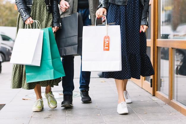 Niedriger abschnitt von freunde, die auf bürgersteig mit bunten einkaufstaschen gehen