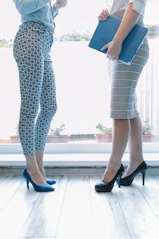 Niedriger abschnitt von zwei geschäftsfrauen, die nahe eingang stehen