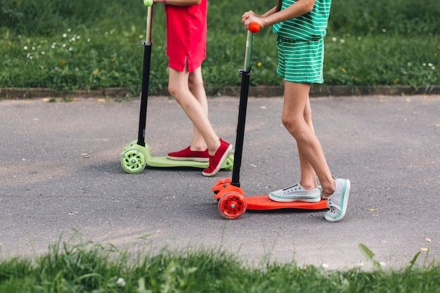 Niedriger abschnitt von zwei mädchen, die trittroller im park reiten