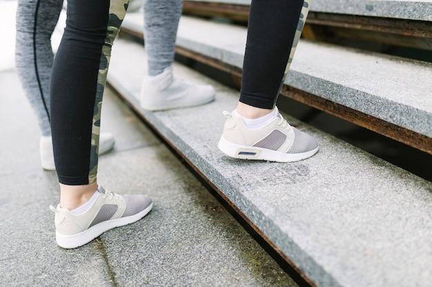 Niedriger abschnitt von zwei weiblichen joggern auf treppenhaus