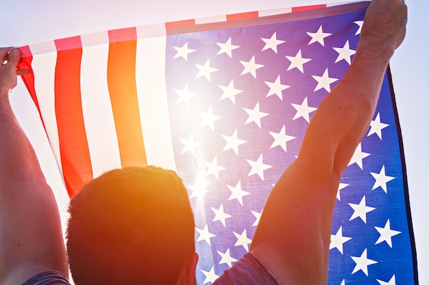 Niedriger blickwinkel auf die erhobenen hände des mannes mit wehender amerikanischer flagge gegen den klaren blauen himmel. unabhängigkeitstag der vereinigten staaten von amerika. konzept des amerikanischen patriotischen volkes