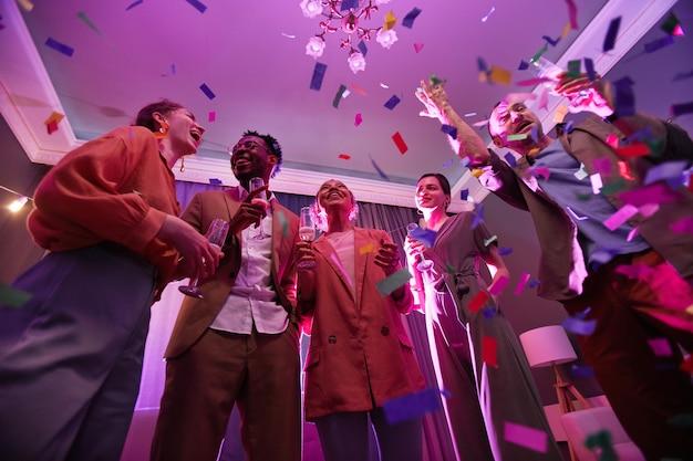 Niedriger blickwinkel auf verschiedene gruppen junger leute, die unter konfettidusche stehen, während sie eine party mit freunden drinnen genießen