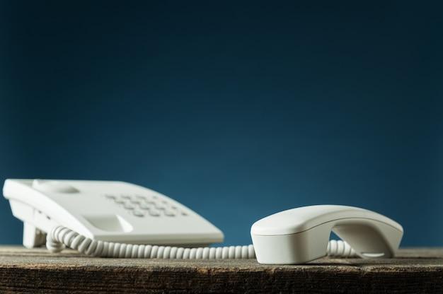 Niedriger blickwinkel auf weißes festnetztelefon mit hörer aus dem haken auf rustikalem holzschreibtisch.
