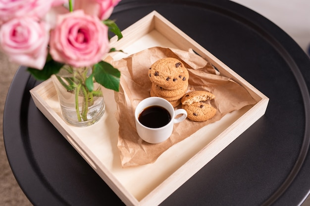 Niedriger quadratischer karton mit tasse kaffee und knusprigen keksen auf papier, bündel rosa rosen im glas auf kleinem schwarzen runden tisch