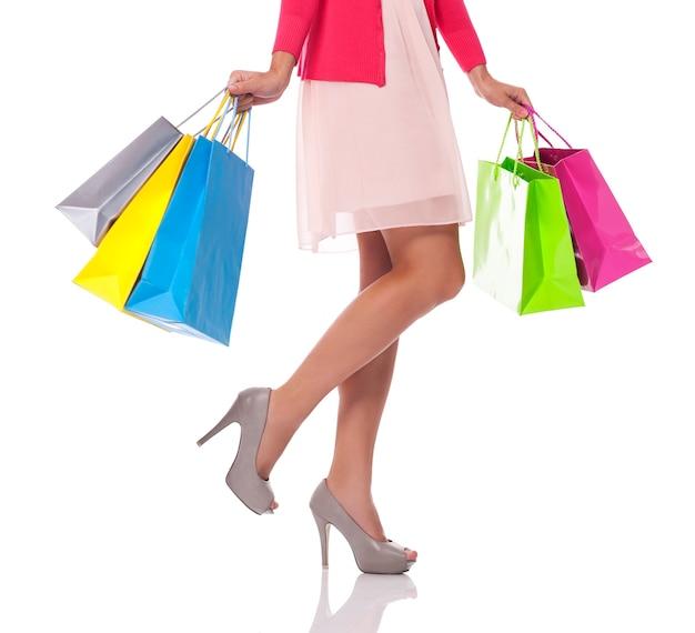 Niedriger teil der frau mit mehrfarbigen einkaufstaschen