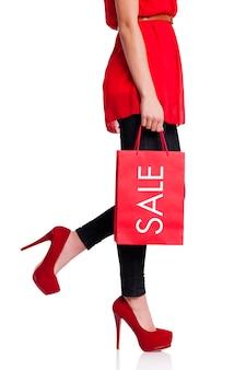 Niedriger teil einer frau mit ihrer roten einkaufstasche