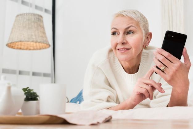Niedriger winkel der älteren frau im bett, das smartphone hält
