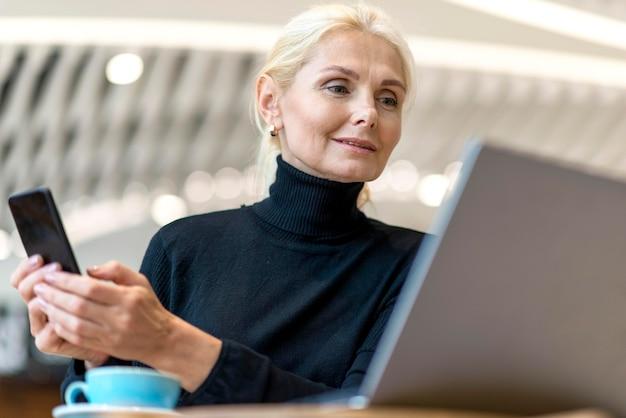 Niedriger winkel der älteren geschäftsfrau, die auf laptop mit smartphone arbeitet