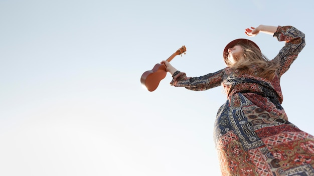 Niedriger winkel der böhmischen frau mit ukulele und kopienraum