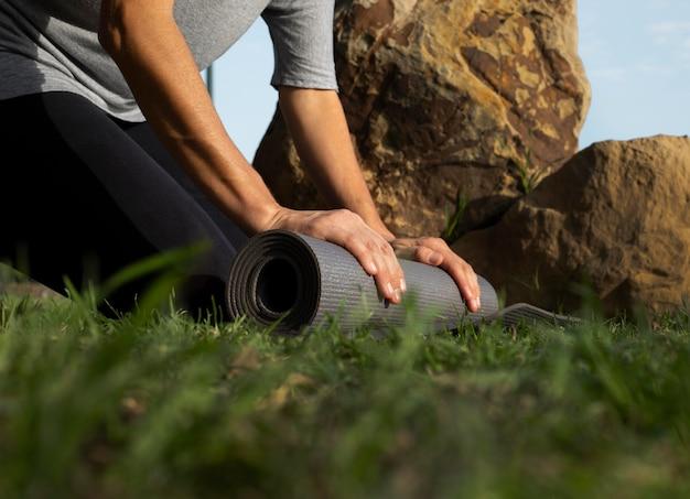 Niedriger winkel der frau, die yogamatte auf dem gras rollt