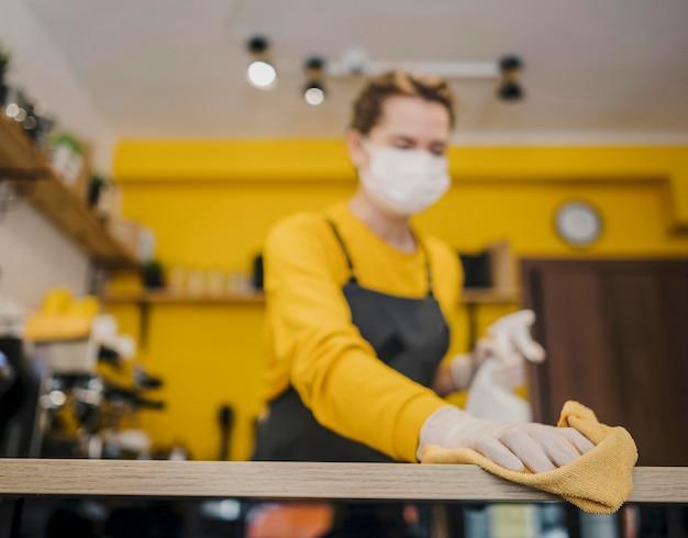 Niedriger winkel der weiblichen barista-reinigung mit medizinischer maske auf