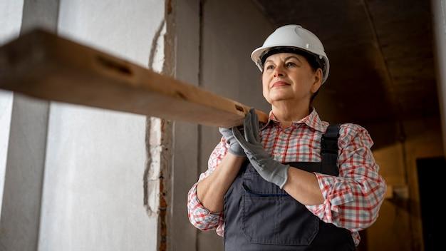 Niedriger winkel der weiblichen bauarbeiterin mit helm