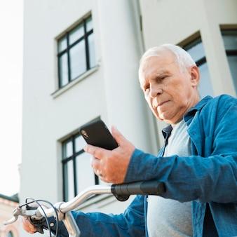 Niedriger winkel des alten mannes mit fahrrad