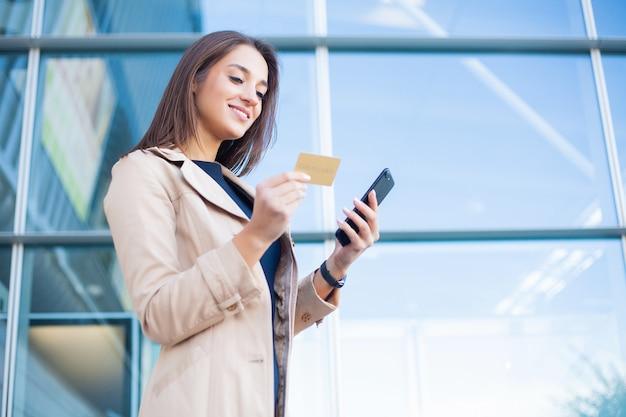 Niedriger winkel des erfreuten mädchens stehend an der flughafenhalle. er verwendet gold kreditkarte und handy für die zahlung