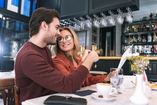 Niedriger winkel des fröhlichen begeisterten paares, das sich zum essen entscheidet und am tisch sitzt