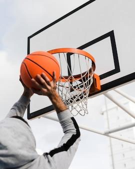 Niedriger winkel des jungen, der in basketballkorb wirft