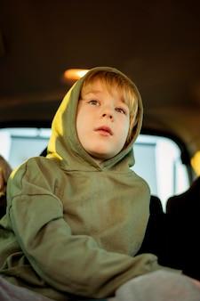 Niedriger winkel des kindes im auto auf einer straßenfahrt