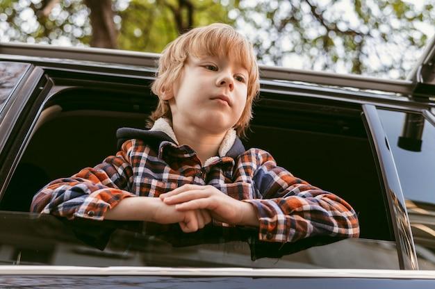 Niedriger winkel des kindes im auto während einer straßenfahrt