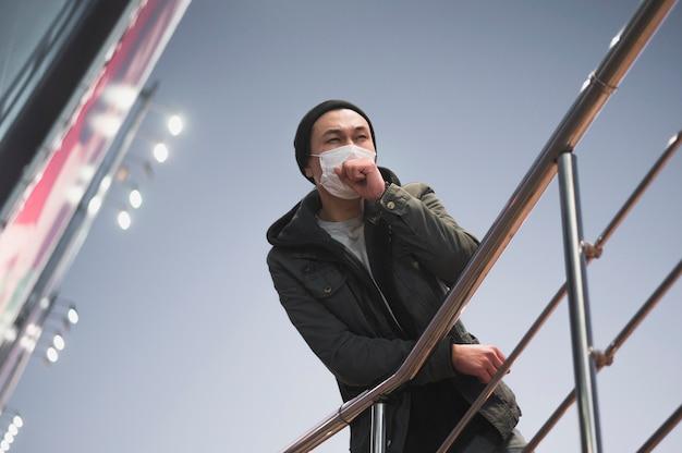 Niedriger winkel des mannes, der hustet, während er eine medizinische maske trägt