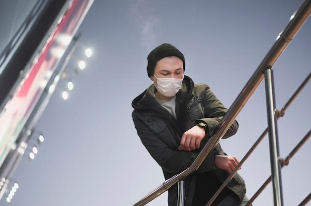 Niedriger winkel des mannes mit medizinischer maske