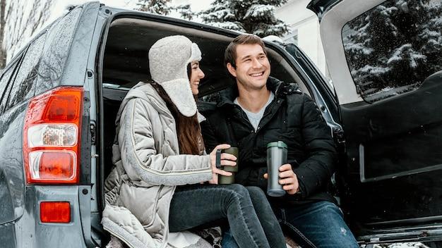 Niedriger winkel des smiley-paares, das während einer straßenfahrt ein warmes getränk im kofferraum des autos trinkt