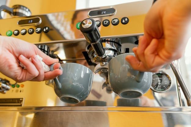 Niedriger winkel des weiblichen barista unter verwendung der kaffeemaschine