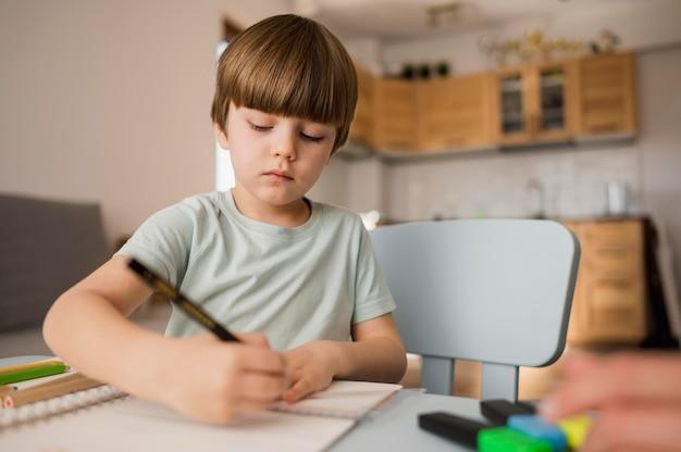 Niedriger winkel des zeichens des kindes auf notizbuch, während zu hause unterrichtet