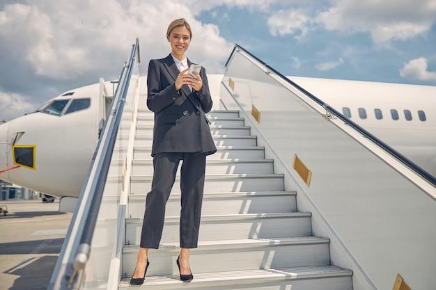 Niedriger winkel einer erfreuten blonden dame, die mit einem gerät auf den flugzeugstufen steht