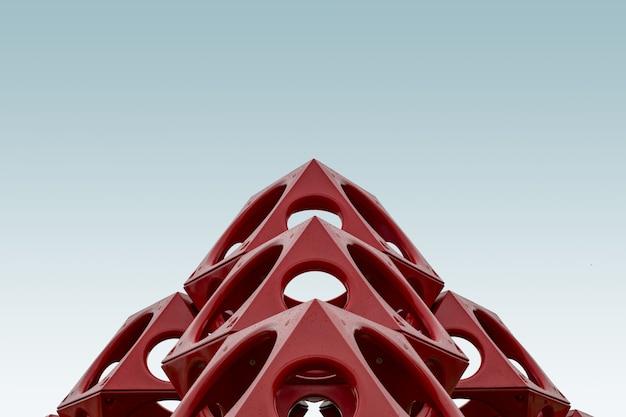 Niedriger winkel einer roten geometrischen struktur unter dem blauen himmel