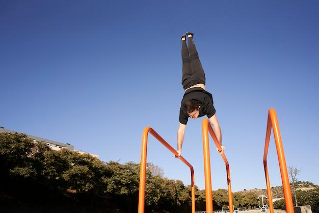 Niedriger winkel eines mannes, der handstand auf der stange tut. bewegung im freien. konzept von gesundem leben, sport, training, krafttraining.