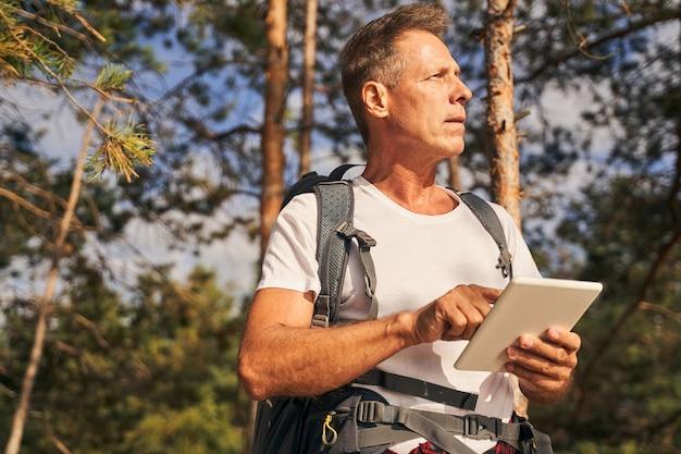 Niedriger winkel eines sportlichen, reifen mannes mit rucksack, der zwischen bäumen steht und beim wandern das touchpad verwendet