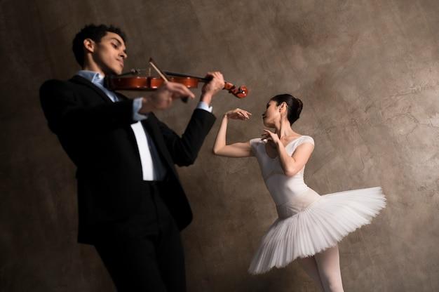 Niedriger winkel von männlichem musiker und ballerina