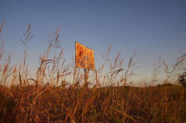 Niedriger winkelschuss der beschilderung in einem landwirtschaftlichen feld mit einem klaren blauen himmel