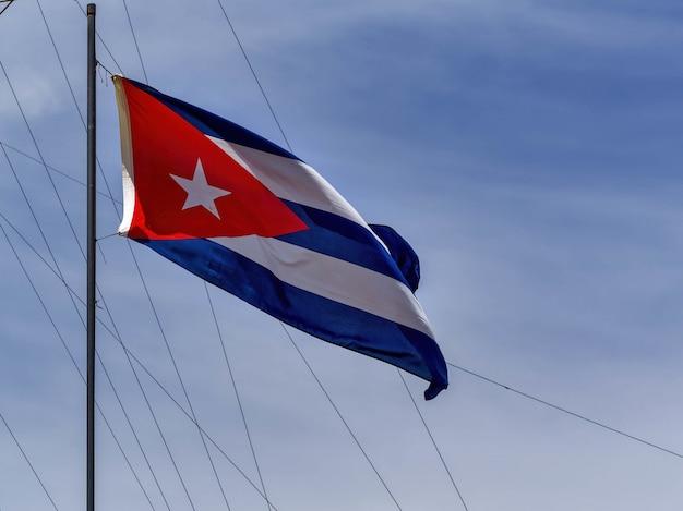 Niedriger winkelschuss der nationalflagge von kuba auf einem fahnenmast