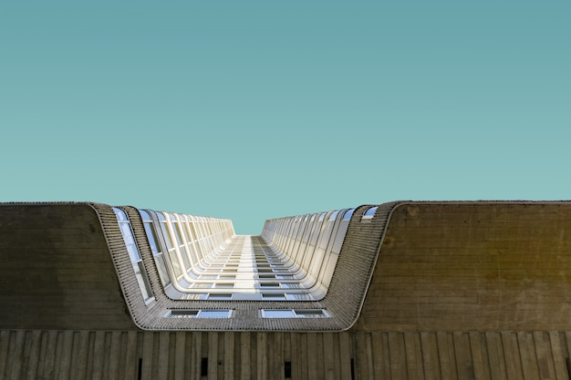 Niedriger winkelschuss des hohen backsteingebäudes unter dem klaren blauen himmel