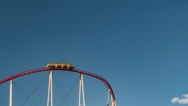 Niedriger winkelschuss einer achterbahn, die unter dem klaren blauen himmel gefangen genommen wird