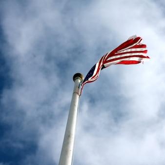 Niedriger winkelschuss einer flagge der vereinigten staaten mit einem bewölkten blauen himmel