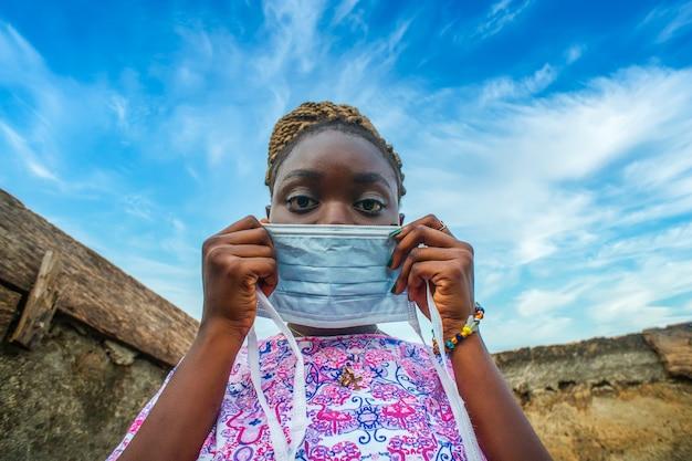Niedriger winkelschuss einer jungen afrikanischen frau, die eine schützende gesichtsmaske aufsetzt