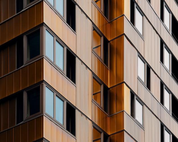 Niedriger winkelschuss eines braunen hochhausgebäudes, das zur tageszeit gefangen genommen wird