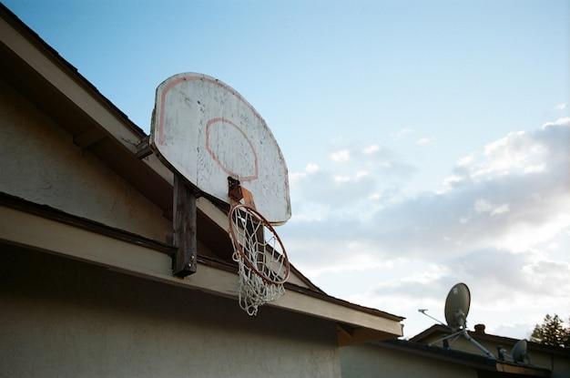 Niedriger winkelschuss eines gebrochenen basketballkorbs auf der oberseite eines hauses